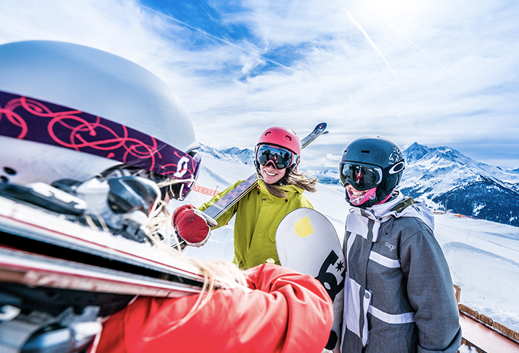 Three skiiers and snowboarders stood infront of a mountainous view smiling.