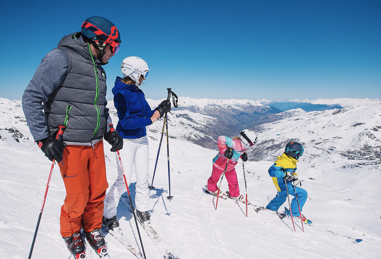 two children are skiing and the parents are watching, infront of a snowy group of mountains.